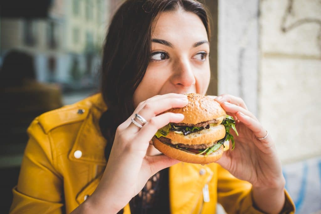 Women eating plant-based protein burger